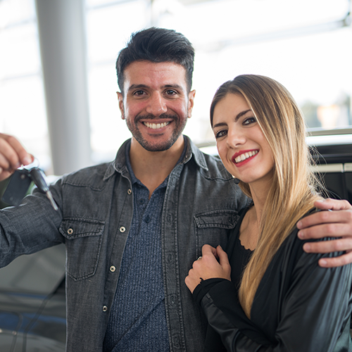 couple smiling with keys being held up